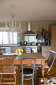 Various chairs around wooden table in rustic kitchen-dining room