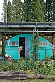 Grüner Wohnwagen unterm Wellblechdach im Garten