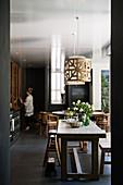 Rustikaler Holztisch mit Hockern und Bank in schwarzer Küche