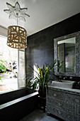 Chest of drawers and mirror frame with mother-of-pearl inlays in black bathroom with bathtub