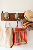 Summer hat, basket and bags hung from coat rack with ducks' feet