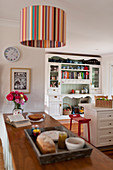 Striped ceiling lamp above counter in country-house kitchen