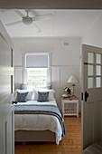 Blick aufs Bett mit blau-weißer Bettwäsche und Nachttisch im Schlafzimmer mit Dielenboden