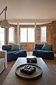 Large blue beanbags and coffee table in living room with bay window and stone wall