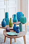 Vases and ceramics ornaments in shades of blue and green on set of 3 side tables
