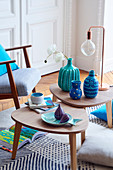 Blue vases, table lamp and fish-shaped plates on side tables