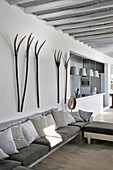 Pitchforks on wall above sofa with scatter cushions in shades of grey