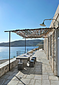 Stone-flagged terrace with sea view under blue sky