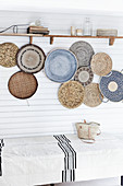 Arrangement of shallow baskets woven from natural materials decorating wall