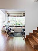 Blick ins Wohnzimmer mit Armlehnstühlen und Sideboard vor Fenster