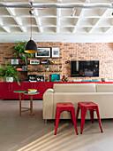 Rote Hocker am Sofa, im Hintergrund rote Unterschränke an Backsteinwand in offenem Wohnraum