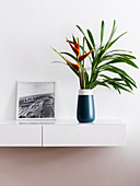 Bird of paradise flowers in vase and picture on floating shelves with integrated drawers