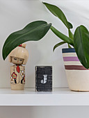 Houseplant and Oriental wooden doll on shelf