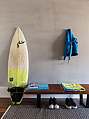 Surfboard next to wooden bench with pairs of shoes below