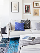 Scatter cushions on pale sofa, pictures and ottoman in living room