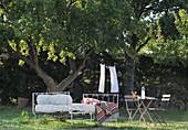 Metallbett und Gartenmöbel unterm Baum im mediterranen Garten