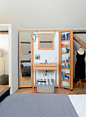 Miniature bathroom with folding doors in bedroom