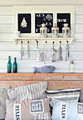 Coat rack with chalkboards and fish ornaments above garden sofa