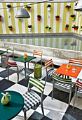 Chairs and bistro tables in restaurant on roof terrace with potted plants on wall
