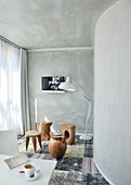 Tree-stump stools or various types and standard lamp in room with grey walls