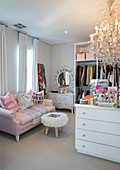 Pink sofa, fur-covered stool, dressing table and chandelier in feminine dressing room