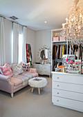 Feminines Ankleidezimmer mit rosa Sofa, Fellhocker, Schminktisch und Kronleuchter