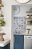 Blick in die Waschküche mit blau gemusterten Fliesen über der Spüle