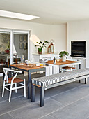 Dining table with bench and chairs in front of fireplace on furnished terrace