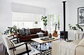 Leder- und Polstermöbel um Couchtisch im Wohnzimmer mit Kaminofen