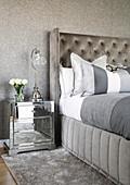 Verspiegeltes Nachtkästchen neben grauem Bett mit hohem Bettkopfteil an grauer Wand