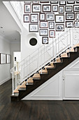 Framed black-and-white family photos on white wall above staircase