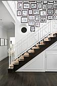 Treppenaufgang mit gerahmten, schwarz-weißen Familienfotos an weißer Wand