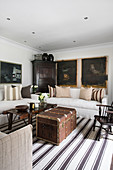 Sofas with linen covers, vintage coffee table, steamer trunk on striped rug and paintings on wall
