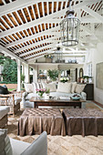 Vintage leather ottoman, coffee table and sofa on roofed veranda