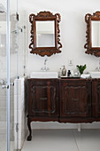 Twin countertop sinks on antique base unit below two mirrored cabinets incorporating antique mirror frames