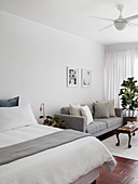 Double bed and grey sofa in open-plan interior