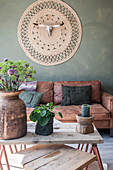 Coffee table, brown leather sofas and wall hanging with animal skull in living room with green wall