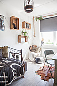 Hanging chair, old wine crates used as shelving modules and metal bed in teenager's bedroom