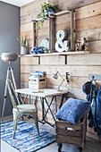 Desk against wooden wall and denim cushions in wooden crate on castors