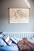 Bed with blue bed linen and sheepskin rug below vintage maps on wall