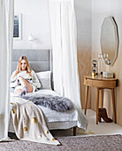 Woman reading in a comfortable canopy bed, a dressing table next door