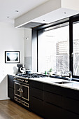 Black kitchenette with gas stove under the panoramic window
