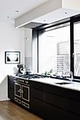 Schwarze Küchenzeile mit Gasherd unter dem Panoramafenster