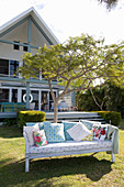 Colourful shabby-chic scatter cushions on bench in summer garden in front of house