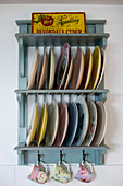 Colourful plates and floral cups on blue, vintage-style plate rack
