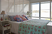 Floral textiles and glass wall in romantic, shabby-chic bedroom