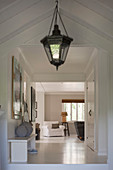 Lantern-style lamp in white, country-house-style hallway with sloping ceiling