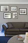 Gallery of black-and-white photos above grey sofa