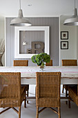 Wicker chairs at shabby-chic table in dining room in country-house style