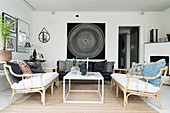 Rattan sofas, coffee table and black leather couch in living room